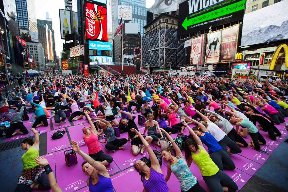 """. People take part in a group yoga practice on the morning of the summer solstice in New York\'s Times Square, June 21, 2013. The \""""Solstice in Times Square\"""" event on Friday brought out thousands of participants to celebrate the year\'s longest day in New York. REUTERS/Lucas Jackson"""