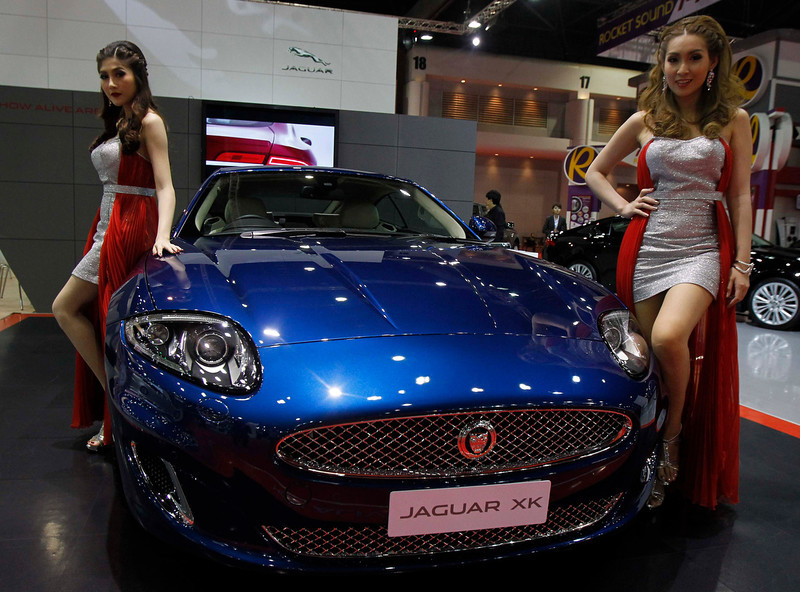 . Models pose beside a Jaguar XK during a media presentation of the 34th Bangkok International Motor Show in Bangkok March 26, 2013. The Bangkok International Motor Show will be held from March 27 to April 7. REUTERS/Chaiwat Subprasom