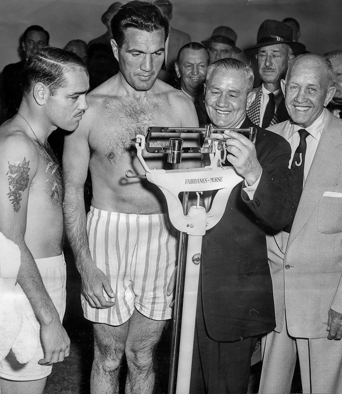""". San Francisco, CA April 13, 1955 - Joey Maxim weighs in for his 10-pound bout at the Cow Palace as his foe middleweight champion Carl \""""Bobo\"""" Olson (left) looks on. Chief Inspector of the State Athletic Commision Willie Ritchie checks the scales with manager Jack Kearns. (Oakland Tribune Photo)"""