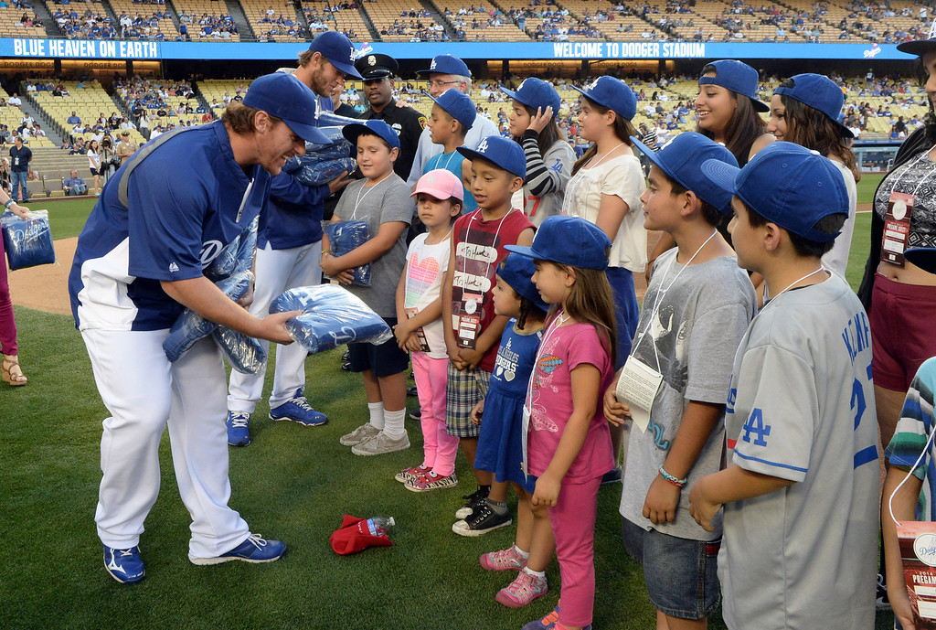. Los Angeles Dodgers starting pitcher Clayton Kershaw and Chad Billingsley hand out blankets to families as members of the San Fernando Valley Rescue Mission are treated to a Major league baseball game between the Miami Marlins and the Los Angeles Dodgers on Wednesday, May 14, 2014 in Los Angeles. The Mission experienced a devastating fire earlier this month. Damage sustained included the destruction of the San Fernando Valley Rescue Mission�s emergency shelter, vehicle fleet, clothing warehouse and food pantry which were vital in aiding those of need in the San Fernando Valley.  (Keith Birmingham/Pasadena Star-News)