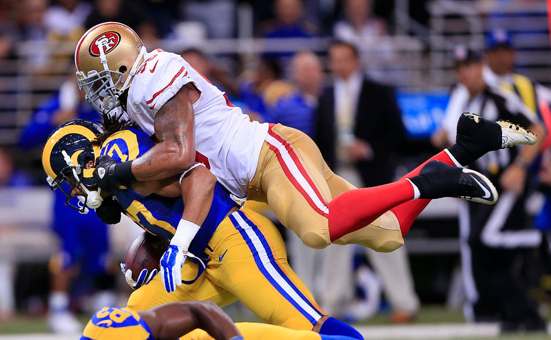 . San Francisco 49ers outside linebacker Ahmad Brooks, top, brings down St. Louis Rams running back Tre Mason (27) in the first quarter of an NFL football game Monday, Oct. 13, 2014, in St Louis. (AP Photo/Billy Hurst)