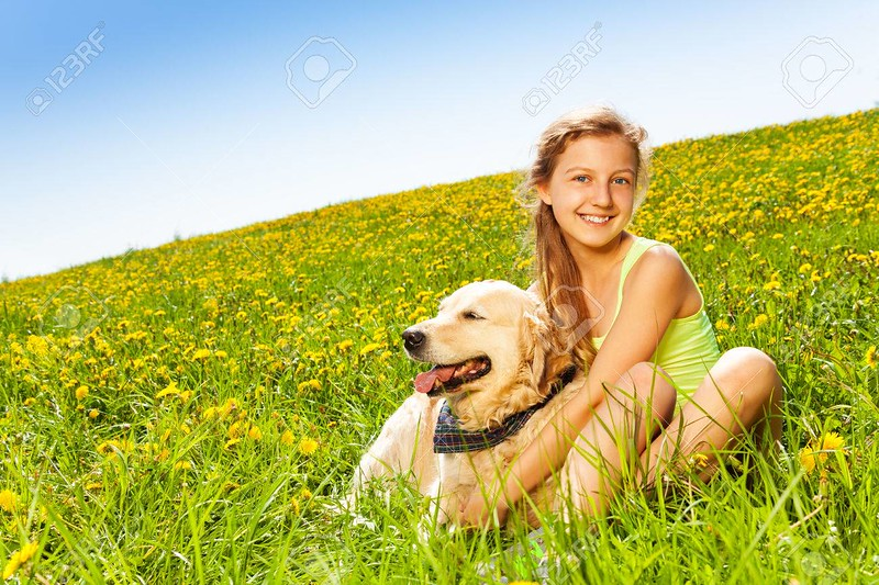 Cute happy girl cuddling dog in summer