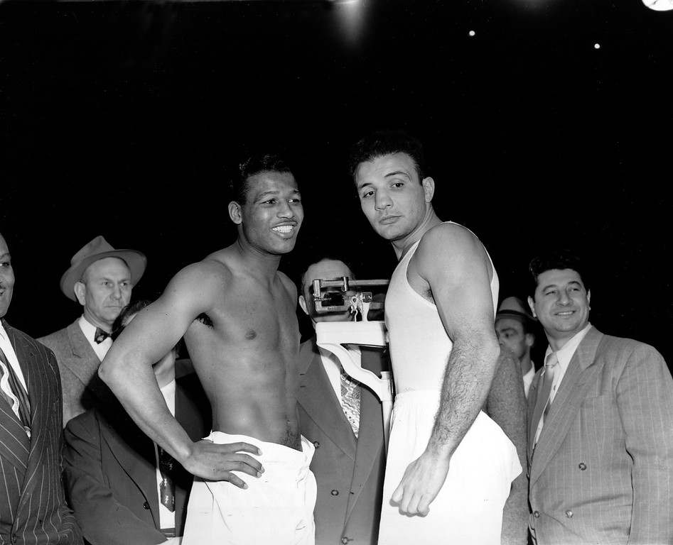 . Middleweight champion Jake LaMotta, right, faces challenger and world welterweight champion Sugar Ray Robinson at the weigh-in for their World Middleweight Championship title bout at Chicago Stadium, Ill., Feb. 14, 1951.  LaMotta weighed in at the limit, 160 pounds, and Robinson scaled 155 1/2.  (AP Photo)