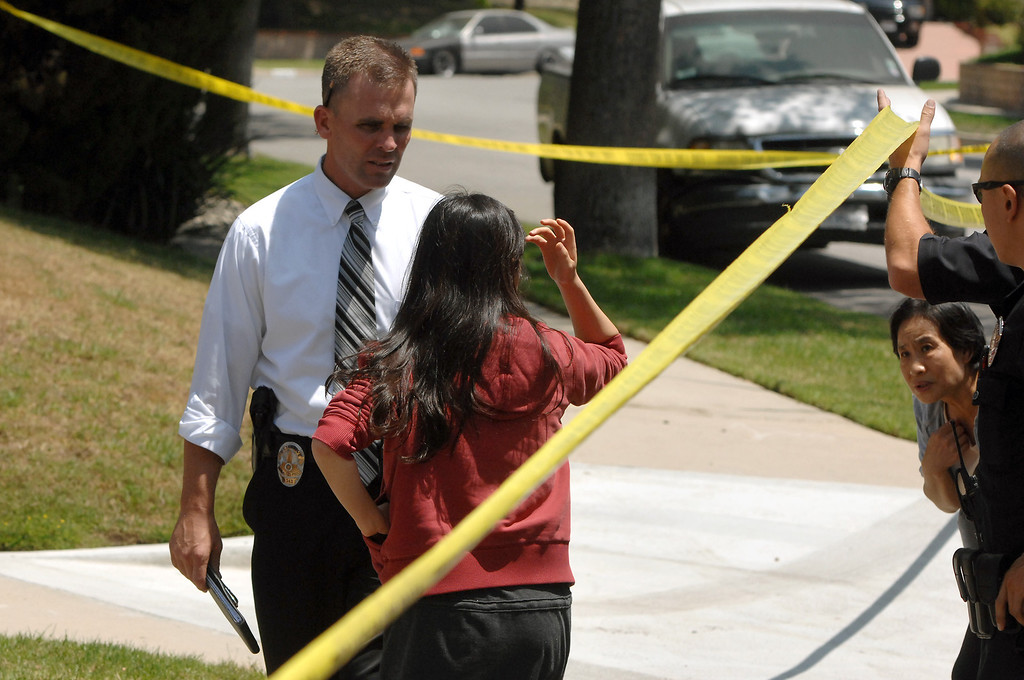 . LAPD detectives let two women pass the crime scene tape  in the 19200 block of Kenya Street in Northridge, Friday, June 15, 2013, where a woman was murdered and the suspect surrendered to SWAT officers following a nighttime standoff. (Michael Owen Baker/Staff Photographer)