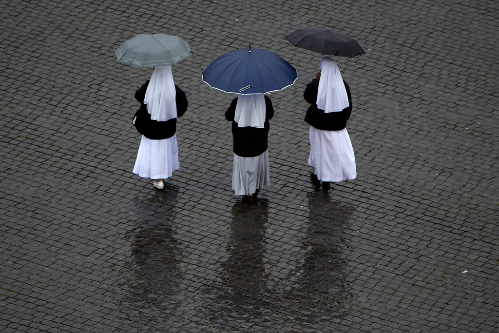 . Nuns walk in the rain at St. Peter\'s Square on  the second day of the conclave to elect a new pope, at the Vatican, Wednesday, March 13, 2013. Cardinals remained divided over who should be pope on Wednesday after three rounds of voting, an indication that disagreements remain about the direction of the Catholic church following the upheaval unleashed by Pope Benedict XVI\'s surprise resignation. (AP Photo/Oded Balilty)