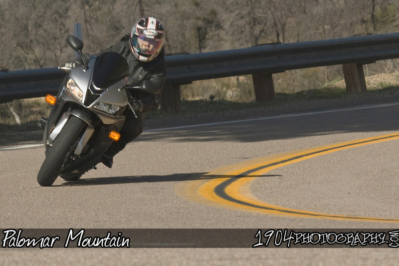 A Girl motorcycle rider heads down south grade road on her Honda CBR on Palomar Mountain.