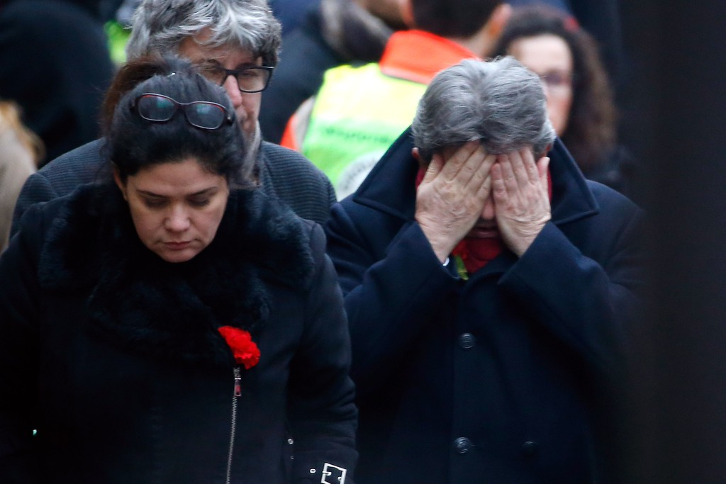 . French far-left leader Jean-Luc Melenchon (R) reacts outside of the headquarters of the French satirical newspaper Charlie Hebdo in Paris on January 7, 2015, after armed gunmen stormed the offices leaving twekve dead. At least 12 people were killed when gunmen armed with Kalashnikovs and a rocket-launcher opened fire in the offices of French satirical weekly Charlie Hebdo on January 7. AFP PHOTO / KENZO  TRIBOUILLARD/AFP/Getty Images