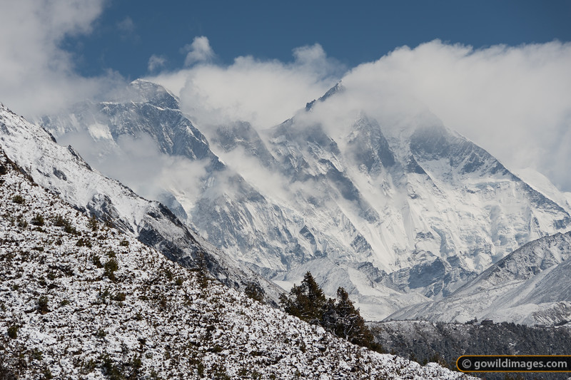 Mt Everest, top left, pokes through the cloud, looming over Tengboche monastery, bottom right
