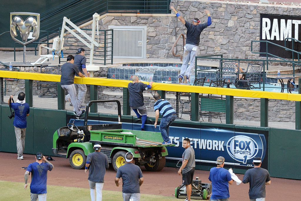 . PHOENIX, AZ - SEPTEMBER 19:  Los Angeles Dodgers players climb the right field fence and jump in the pool after clinching the National League West after a 7-6 win against the Arizona Diamondbacks at Chase Field on September 19, 2013 in Phoenix, Arizona.  (Photo by Norm Hall/Getty Images)
