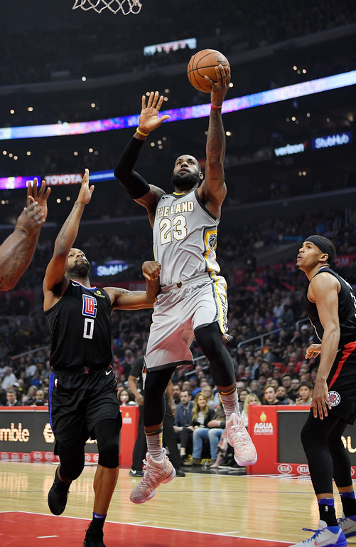 . Cleveland Cavaliers forward LeBron James, center, shoots as Los Angeles Clippers guard Sindarius Thornwell, left, and forward Tobias Harris defend during the first half of an NBA basketball game, Friday, March 9, 2018, in Los Angeles. (AP Photo/Mark J. Terrill)