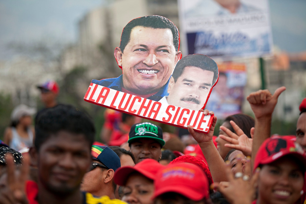 ". A supporter holds up a sign that reads in Spanish ""The fight continues\"" and shows late President Hugo Chavez, left, and current presidential candidate Nicolas Maduro, before the closing campaign rally for Maduro in Caracas, Venezuela, Thursday, April 11, 2013. Maduro, Chavez\'s hand-picked successor, is running for president against opposition candidate Henrique Capriles on April 14. (AP Photo/Ramon Espinosa)"