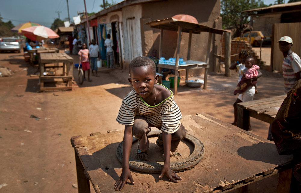 Description of . A young boy plays with a tire on a wooden stall at the market in the Bimbo neighborhood of the capital Bangui, Central African Republic, Tuesday, Jan. 1, 2013. President Francois Bozize's government is coming under growing threat as rebels vowing to overthrow him rejected appeals from the African Union to hold their advance and try to form a coalition government. (AP Photo/Ben Curtis)