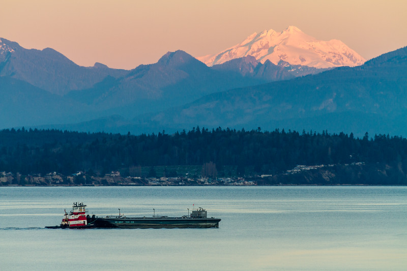 View of US Navy ship with mountains in background at sunrise