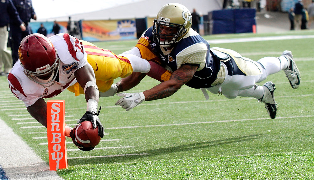 Description of . Southern California running back Silas Redd, left, dives into the end zone past Georgia Tech's Louis Young during the Sun Bowl NCAA college football game, Monday, Dec. 31, 2012, in El Paso, Texas. (AP Photo/The El Paso Times, Mark Lambie)