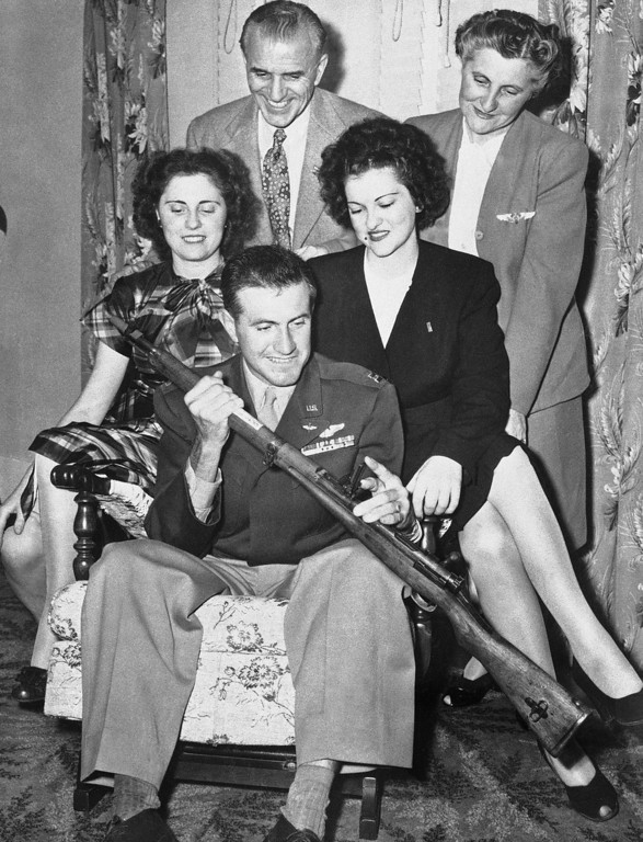 . Capt. Louis Zamperini (seated), former Japanese prisoner of war and Olympic distance runner, shows his family a Japanese rifle at a long-delayed Christmas Party which was held on his return to his home in Torrance, Calif., on Oct. 6, 1946. Zamperini, an army bombardier, spent 47 days on a life raft and then 28 months in Japanese prison camps. Left to right: A sister, Mrs. Sylvia Flammer; father, Anthony Zamperini; a sister, Virginia Zamperini and mother, Louise. (AP Photo/LA)
