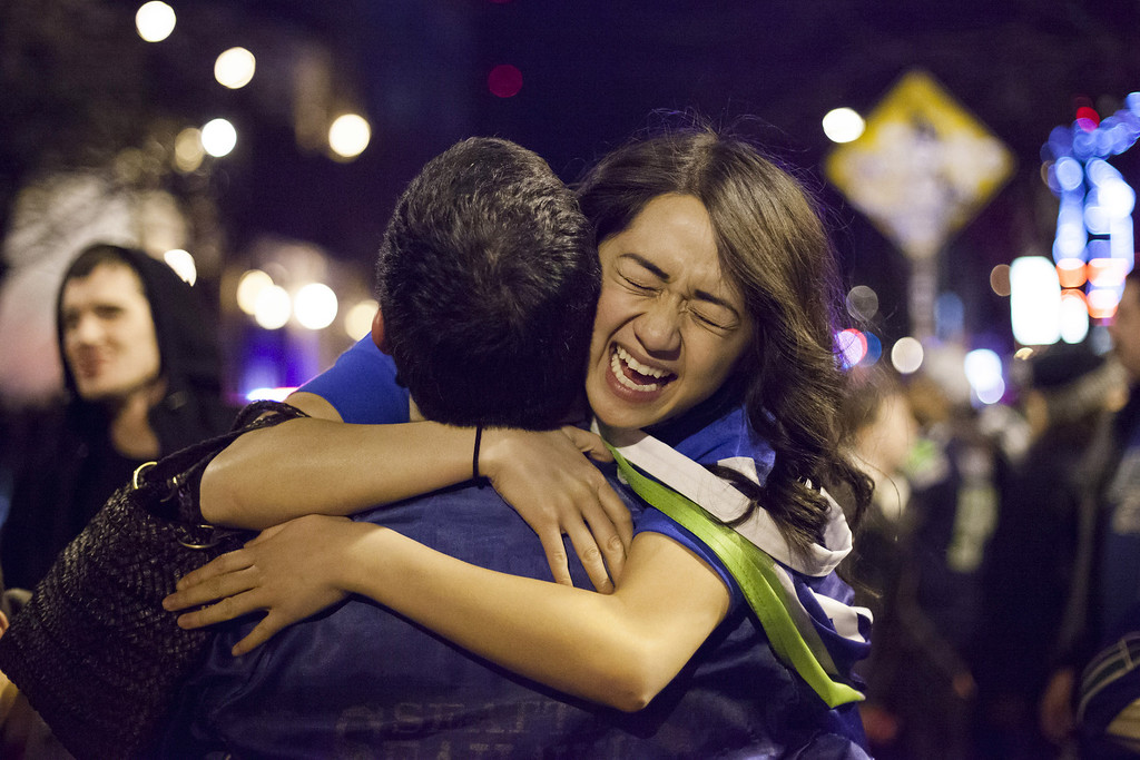 . Seattle Seahawks fans embrace in the street after watching their team win the Super Bowl on February 2, 2014 in Seattle, Washington. The Seahawks defeated the Denver Broncos 43-8 in Super Bowl XLVIII.  (Photo by David Ryder/Getty Images)