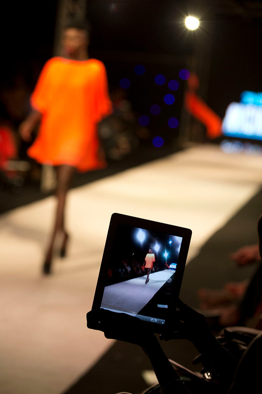 . A spectator films with a tablet as a model wears a design by Adama Paris of Senegal, during the final runway show of Dakar Fashion Week, at Hotel des Almadies, in Dakar, Senegal, in the early morning hours of Sunday, June 23, 2013. After a Friday runway show held in a dusty marketplace in the working class suburb of Guediawaye, Dakar Fashion Week closed Saturday night with a finale at a luxury hotel that showcased the work of 14 designers from West Africa, Europe, South America, and the Caribbean. (AP Photo/Rebecca Blackwell)