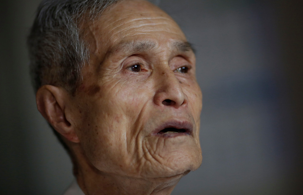 . FILE - In this June 30, 2015 file photo, Sumiteru Taniguchi, a survivor of the 1945 atomic bombing of Nagasaki, speaks about his experience during an interview at his office in Nagasaki, southern Japan. Taniguchi, who devoted his life to seeking to abolish nuclear weapons after he was burned severely in the 1945 attack on Nagasaki, has died of cancer in his hometown in southern Japan. He died Aug. 30 at age 88. Taniguchi died of cancer Wednesday at a hospital in Nagasaki, where he had been treated for the illness, according to the Japan Confederation of A- and H-Bomb Sufferers Organizations. (AP Photo/Eugene Hoshiko, File)