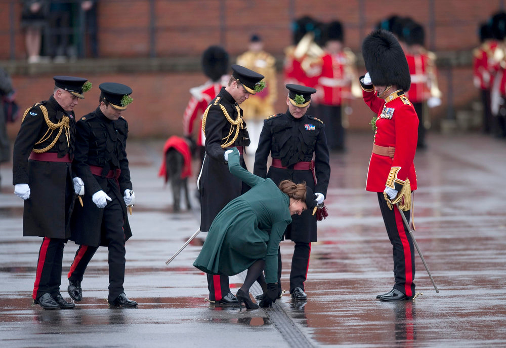 . Britain\'s Prince William (C) supports his wife Catherine, Duchess of Cambridge as she pulls her heel from a grate during a visit on St Patrick\'s Day to Mons Barracks in Aldershot, southern England March 17, 2013. REUTERS/Kieran Doherty