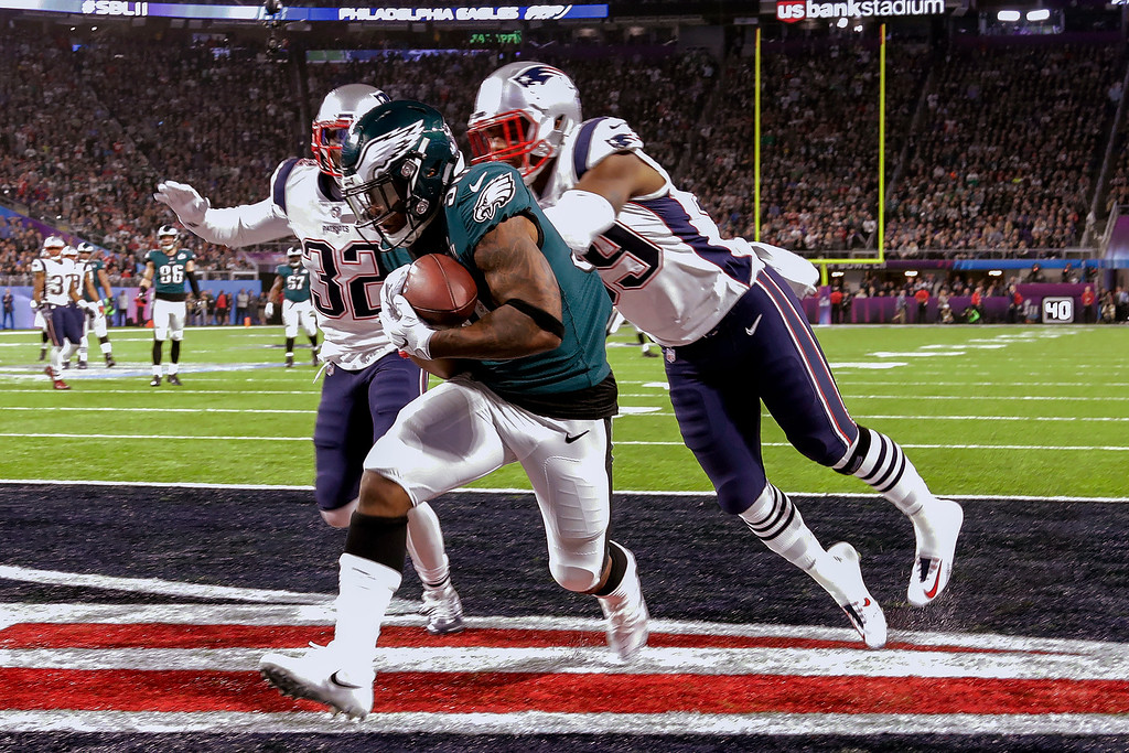 . Philadelphia Eagles running back Corey Clement (30) scores a touchdown, as New England Patriots cornerback Johnson Bademosi (29) and free safety Devin McCourty (32) are late with the tackle, during the second half of the NFL Super Bowl 52 football game, Sunday, Feb. 4, 2018, in Minneapolis. (AP Photo/Chris O\'Meara)