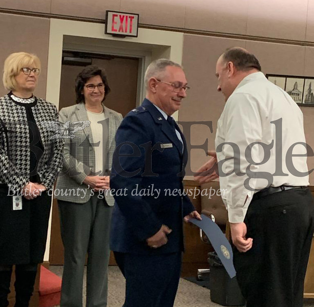 Capt. Rex Cox of Zelienople, middle, finishes his salute before shaking hands with county Director of Veterans Affairs, John Cyprian, right.