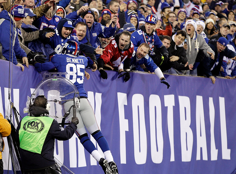 Description of . New York Giants tight end Martellus Bennett celebrates his 6-yard touchdown reception with fans during the first half of an NFL football game against the New Orleans Saints, Sunday, Dec. 9, 2012, in East Rutherford, N.J. (AP Photo/Kathy Willens)