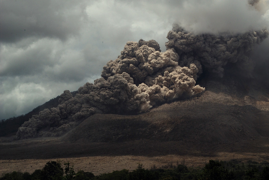 . Dark giant ash clouds rise from the crater of Mount Sinabung volcano during an eruption on October 8, 2014, as seen from Karo district located on Indonesia\'s Sumatra island, following an earlier eruption on October 5, 2014. AFP PHOTO / SUTANTA  ADITYA/AFP/Getty Images