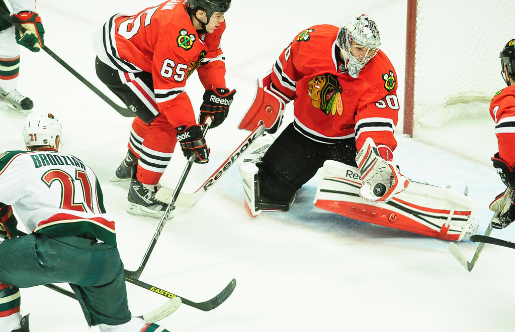 . Blackhawks goalie Corey Crawford makes a save on a shot from Wild center Kyle Brodziak, left, late in the first period. Chicago center Andrew Shaw is at top left.  (Pioneer Press: Ben Garvin)