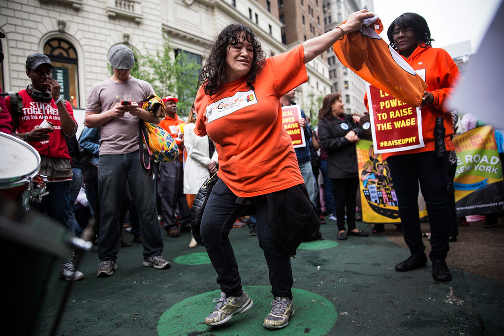 . Protesters demanding higher wages for fast food workers dance to the music of a drum circle during a massive rally on May 15, 2014 in New York City.  (Photo by Andrew Burton/Getty Images)