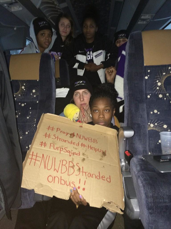 . This photo provided by Chelsea Andorka, the Niagara University women\'s basketball team spokeswoman, shows the team holding a sign while their bus was snowbound on the New York State Thruway in the middle of a lake-effect storm that has dropped more than 4 feet of snow near Lackawanna, N.Y., Tuesday, Nov. 18, 2014. Andorka says the team\'s bus was headed back from a loss in Pittsburgh when it came to a halt at 2 a.m. Tuesday about two miles from the Lackawanna exit near Buffalo. About 25 people are on the bus, including 15 players plus staff, the coach and coach\'s family. (AP Photo/Chelsea Andorka)