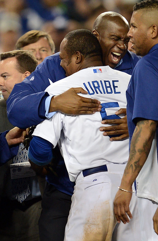 . Dodgers\' owner Magic Johnson hugs Juan Uribe after the final out against  the Atlanta Braves during game 4 of the NLDS at Dodger Stadium Monday, October 7, 2013. The Dodgers beat the Braves 4-3.(Photo by Hans Gutknecht/Los Angeles Daily News)