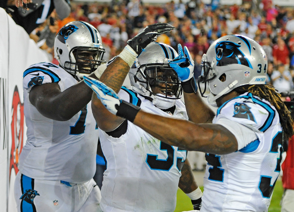 . Carolina Panthers fullback Mike Tolbert, center, celebrates a 3-yard touchdown pass play against the Tampa Bay Buccaneers with tackle Byron Bell, left, and running back DeAngelo Williams during the second half of an NFL football game in Tampa, Fla., Thursday, Oct. 24, 2013. (AP Photo/Brian Blanco)