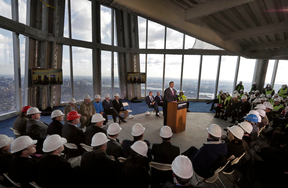 Description of . Legends Chairman & CEO David Checketts, at podium center, of the company that will run the observation deck on the 100th floor of the One World Trade Center building, address a news conference in the venue, in New York, Tuesday, April 2, 2013. The observation deck, that will not open until 2015, will occupy the tower's 100th through 102nd floors. Elevators will whisk visitors to the top in just one minute but the experience of visiting the attraction will take an hour. (AP Photo/Richard Drew)