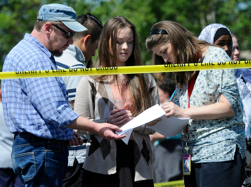 . Students are checked off by staff as they arrive by bus to meet their parents and/or family at the Fred Meyer grocery store parking lot in Wood Village, Ore., after a shooting at Reynolds High School Tuesday, June 10, 2014, in nearby Troutdale. (AP Photo/Greg Wahl-Stephens)