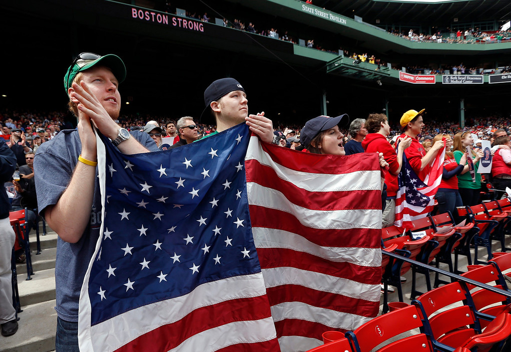 . Fans hold an American flag during ceremonies in tribute of victims and first responders to the Boston Marathon bombings before a baseball game between the Boston Red Sox and the Kansas City Royals in Boston, Saturday, April 20, 2013. (AP Photo/Michael Dwyer)