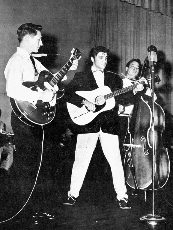 . ** FILE ** In this 1957 file photo, Elvis Presley performs on tour in the summer of 1957, with Scotty Moore on guitar, left, and Bill Black on the stand up bass, right.  (AP Photo, file)