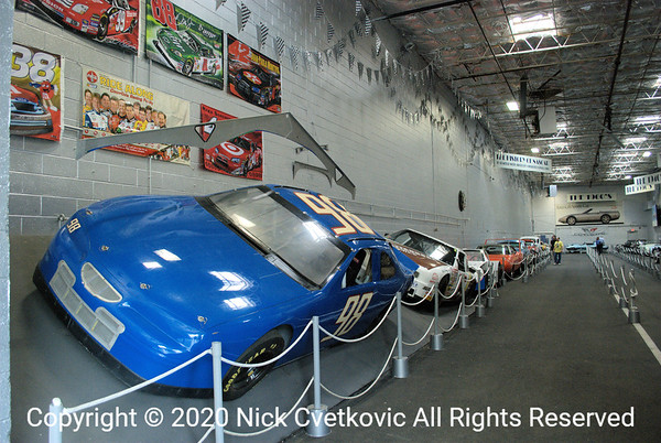 A small collection of NASCAR historical cars is along the other wall