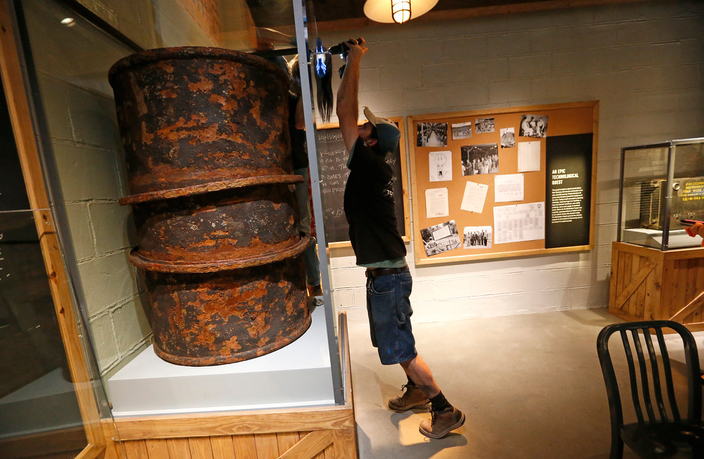 ". Carpenter Brian McKelligott finishes an installation of a heavy water barrel in a mockup of a Manhattan Project classroom as part of the permanent exhibit ""Salute to the Home Front\"" at the National World War II Museum which will open to the public this Saturday, in New Orleans, Monday, June 5, 2017. The exhibit tells the home front story from the 1920s to the development of the atomic bomb. (AP Photo/Gerald Herbert)"