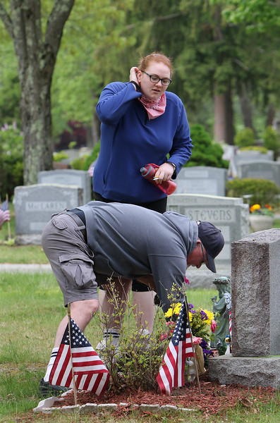 Mark Babcock of Tyngsboro, with his daughter Leanne Babcock, also of Tyngsboro, brings flowers to the grave of his parents and sister at Tewksbury Cemetery, on Saturday of Memorial Day weekend, It was the third anniversary of the death of his father, a Marine veteran of Korea. (SUN/Julia Malakie)