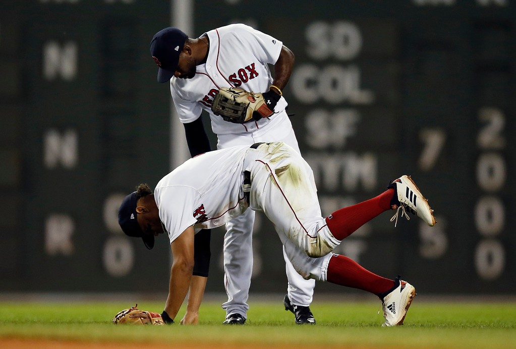 . Boston Red Sox\'s Xander Bogaerts gets up slowly in front of Jackie Bradley Jr. after failing to stop a ball that got past Ian Kinsler on a steal by Cleveland Indians\' Jose Ramirez during the seventh inning of a baseball game in Boston, Tuesday, Aug. 21, 2018. (AP Photo/Michael Dwyer)