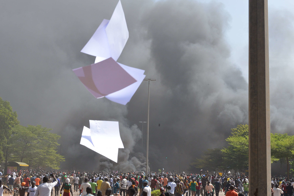 . Documents thrown by protesters fly outside the parliament in Ouagadougou on October 30, 2014 as cars and documents burn. ISSOUF SANOGO/AFP/Getty Images