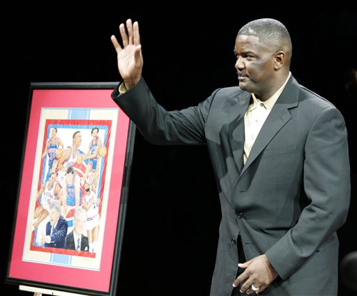 Description of . Detroit Pistons President Joe Dumars acknowledges the crowds applause as he is honored at The Palace during a ceremony during halftime of their game against the Golden State Warriors Friday, Dec. 23, 2005, in Auburn Hills, Mich. Dumars, helped lead the team two NBA Championship titles in 1989 and 1990, now directs them from the front office. (AP Photo/Duane Burleson)
