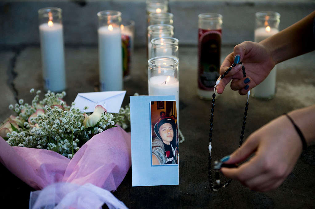 . Justine Sarmiento, 17, places a rosary at a makeshift memorial for Cristopher Rossi, 16, outside his Duarte apartment on Tuesday, Dec. 24, 2013. Rossi was fatally shot outside his home Monday night. (Staff photo by Watchara Phomicinda/ San Gabriel Valley Tribune)