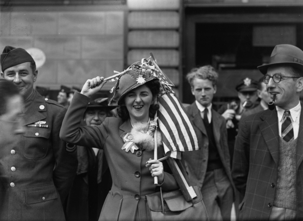 . 8th May 1945:  A woman holding an American flag over her head during VE day celebrations in Piccadilly Circus, London.  (Photo by John F. Stephenson/Topical Press Agency/Getty Images)