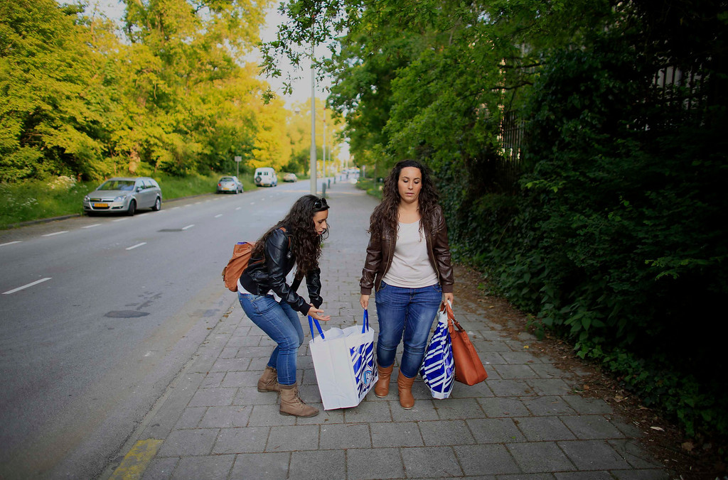 . Spanish nurses Maria Jose Marin (L), 23, and her twin sister Maria Teresa carry shopping bags in The Hague, June 5, 2013. After months of studying Dutch, a group of young Spanish nurses moved to the Netherlands to take up work, fleeing a dismal job market at home. Spain\'s population dropped last year for the first time on record as young professionals and immigrants who moved here during a construction boom head for greener pastures. Spain\'s jobless rate is 27 percent, and more than half of young workers are unemployed. For Spanish nurses, the Netherlands\' nursing deficit is a boon. Picture taken June 5, 2013.  REUTERS/Marcelo del Pozo