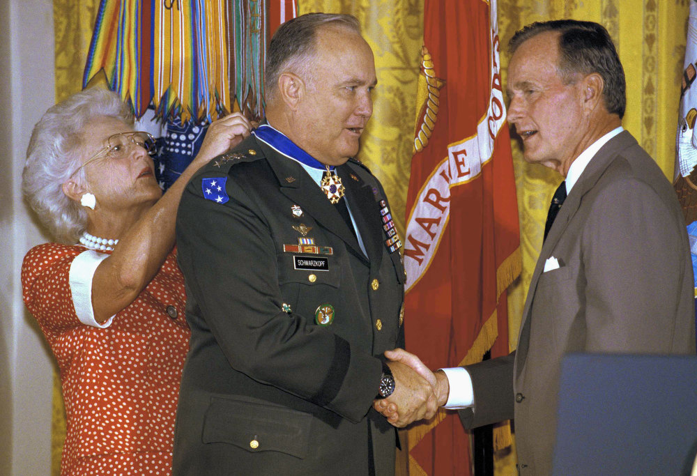 Description of . President George H. Bush shakes hands with Desert Storm commander, Gen. Norman Schwarzkopf, as first lady Barbara Bush pins the Medal of Freedom on the general during a White House ceremony in Washington, Wednesday, July 3, 1991. (AP Photo/Doug Mills)
