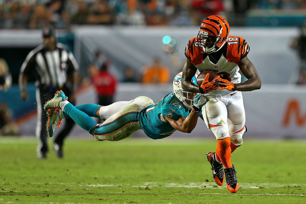. A.J. Green #18 of the Cincinnati Bengals pushes off of Brent Grimes #21 of the Miami Dolphins during a game at Sun Life Stadium on October 31, 2013 in Miami Gardens, Florida. (Photo by Mike Ehrmann/Getty Images)