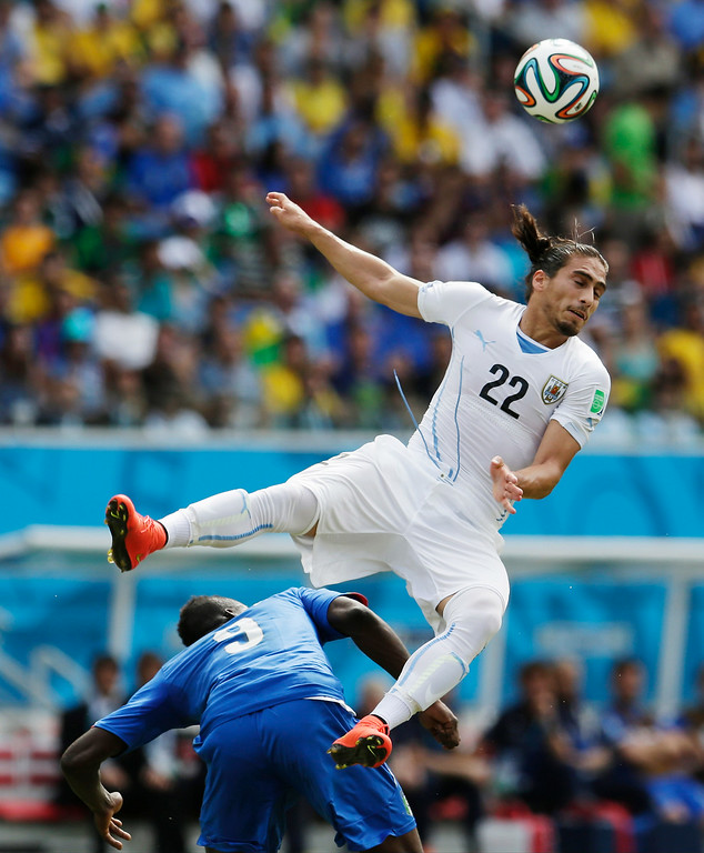 . Italy\'s Mario Balotelli gets underneath Uruguay\'s Martin Caceres as he tries to head the ball during the group D World Cup soccer match between Italy and Uruguay at the Arena das Dunas in Natal, Brazil, Tuesday, June 24, 2014. (AP Photo/Petr David Josek)