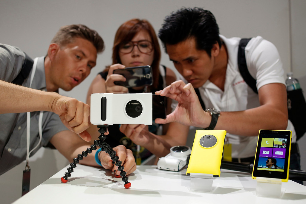. Guests at Nokia\'s unveiling of its new Lumia 1020 smartphone use the new phone\'s 41-megapixel camera with a grip in New York July 11, 2013.  REUTERS/Shannon Stapleton