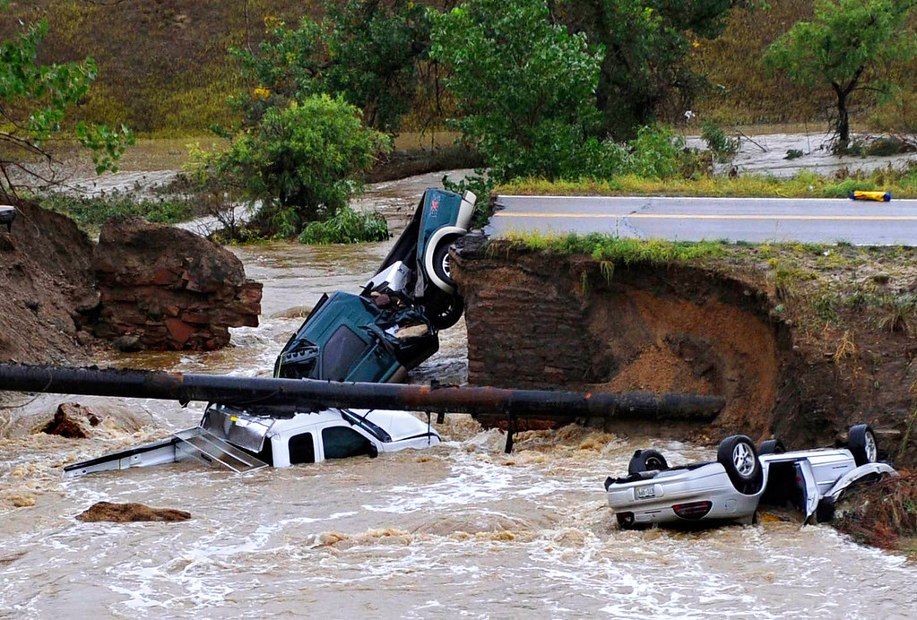 . Three vehicles lie in a creek after raging floodwater undercut Dillon Road near U.S. 287 in Broomfield, Colo. on Sept. 12, 2013. The three motorists were rescued from the vehicles after emergency workers secured the vehicles with ropes and the motorists scrambled up the banks of the creek.